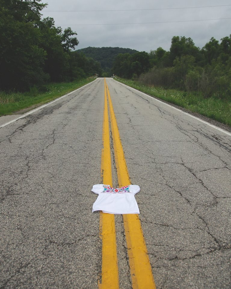 Double yellow lines stretch down a long road surrounded by dense green woods. In the foreground a white blouse with floral embroidery lays in the middle of the road.