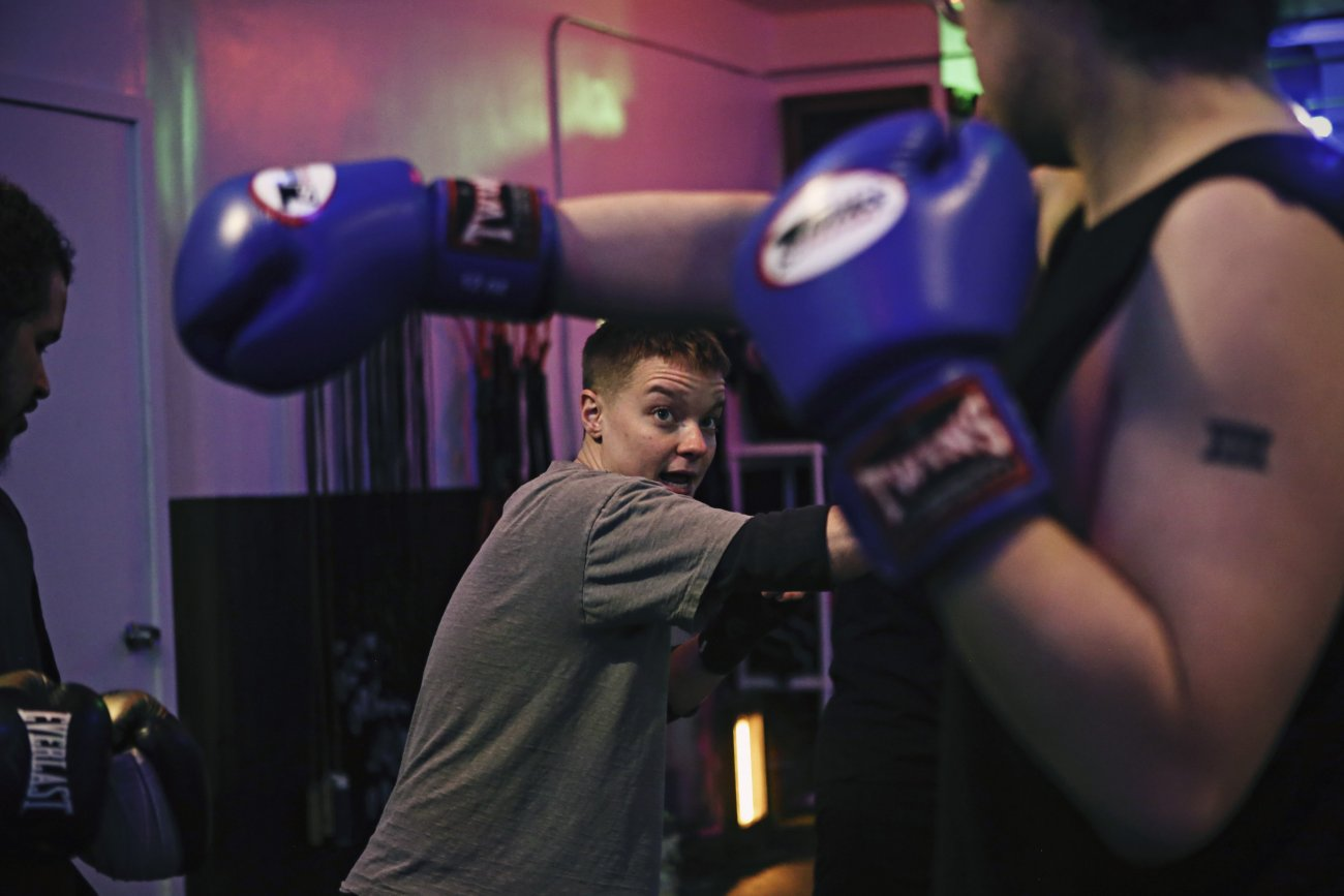 camera faces the artist who is in the center of the image standing in a boxing gym teaching a person on the right hand foreground of the image to throw a right cross.