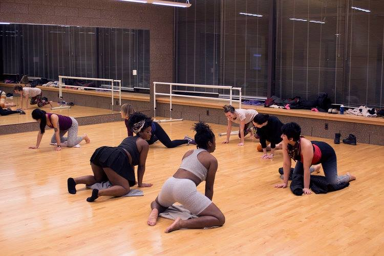 A group of people in a dance studio on their knees learning the fundamentals of twerking.