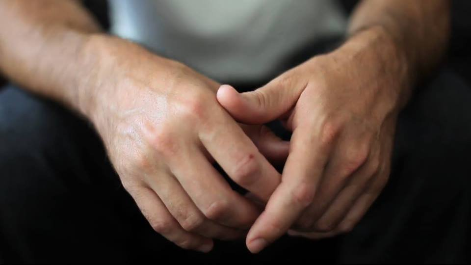 A close up image of hands resting in a lap in a forward position. The hands are presumed to be those of an anonymous white male.