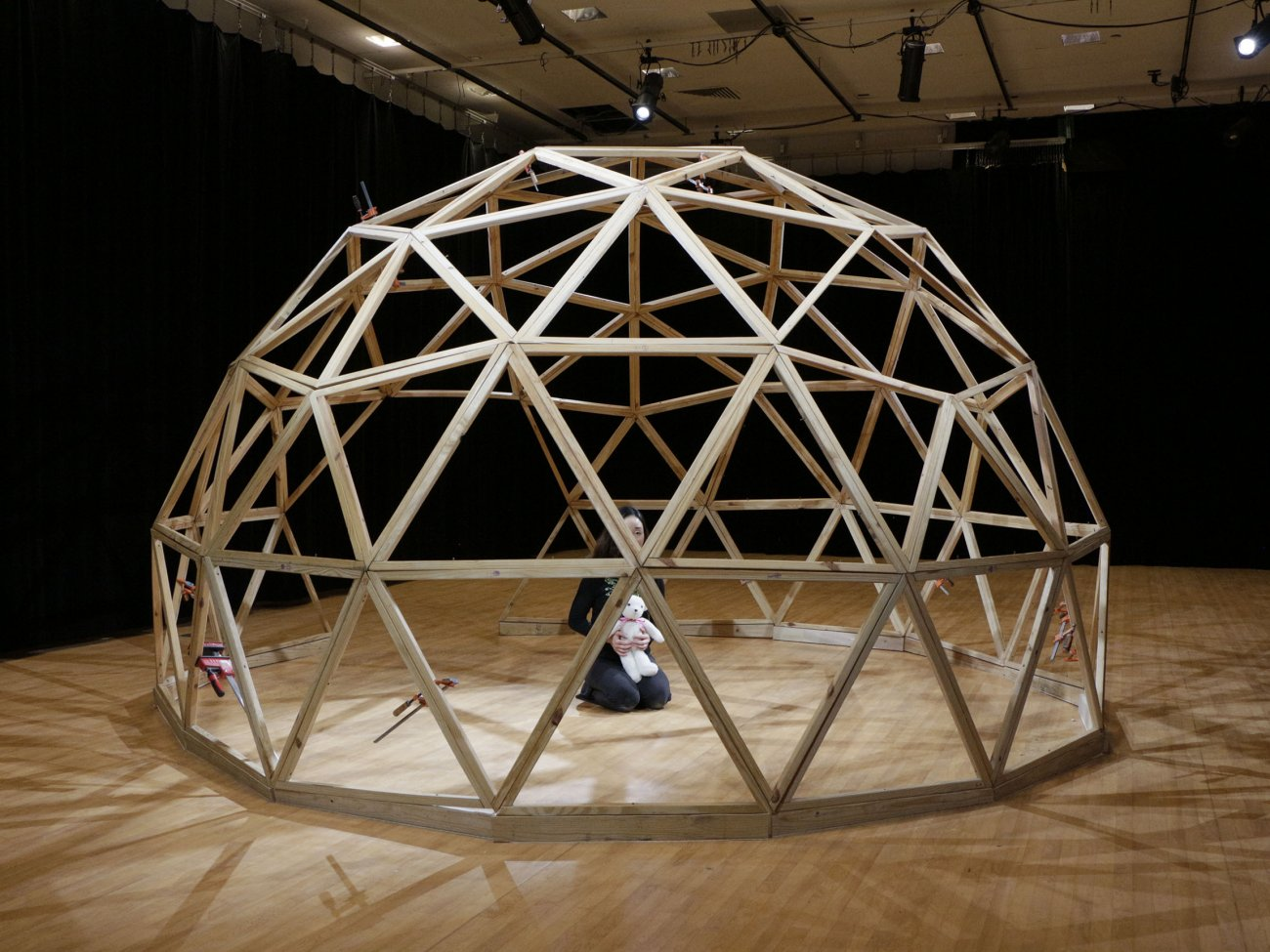 Photograph of a large geodesic dome made of wood, a person is crouched on their knees inside of the dome holding a stuffed animal