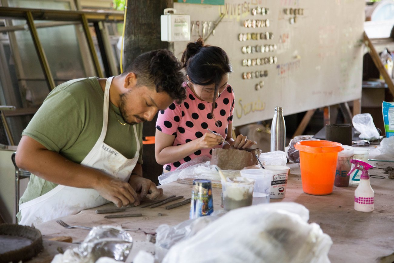 Two artists working with clay in the ceramics studio