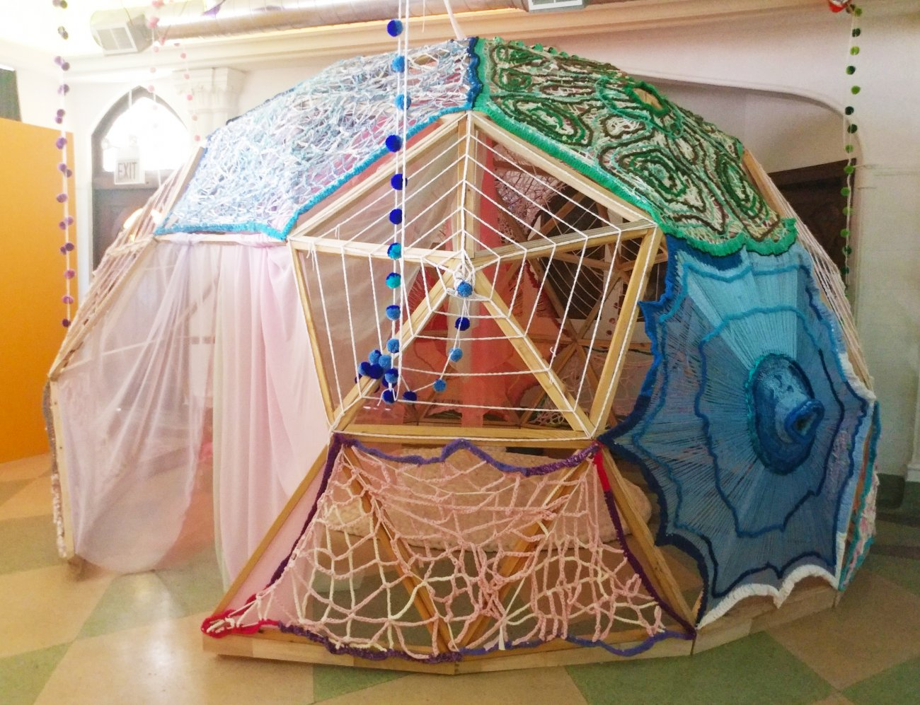 Photograph of geodesic dome covered in a variety of fabrics and crocheted materials.