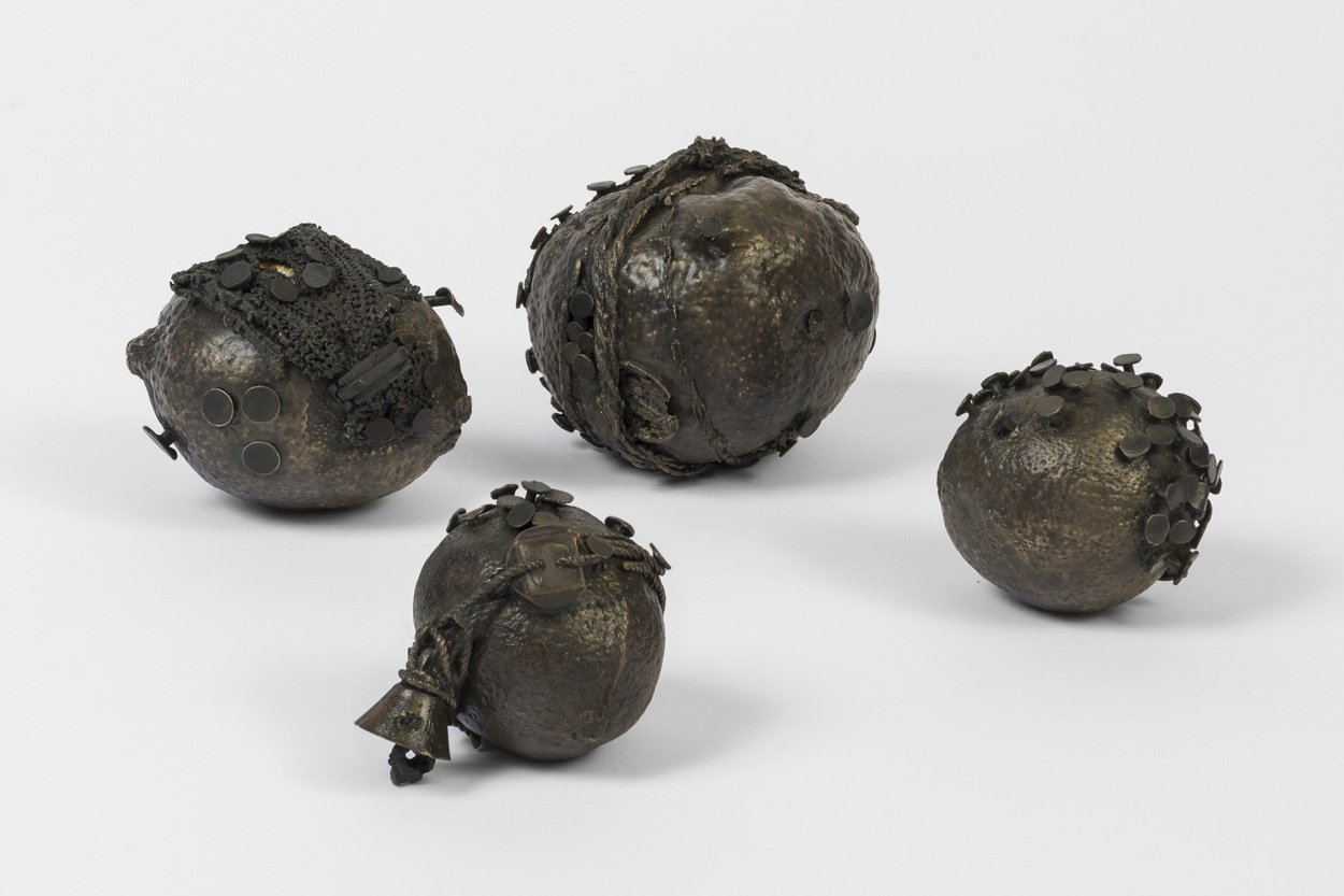 Photograph of four circular cast bronze objects with nails and other materials sticking out of them