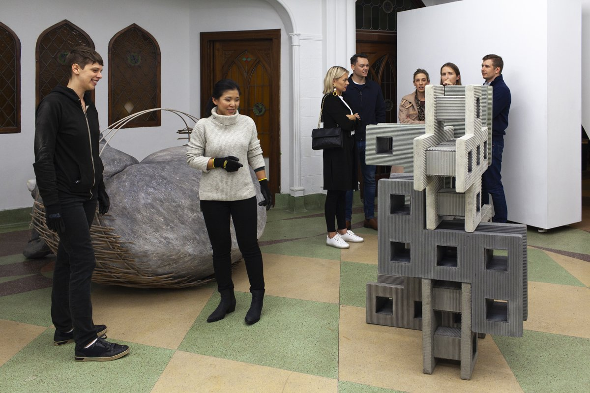 Gallery visitors building structures with gray blocks as part of exhibition installation