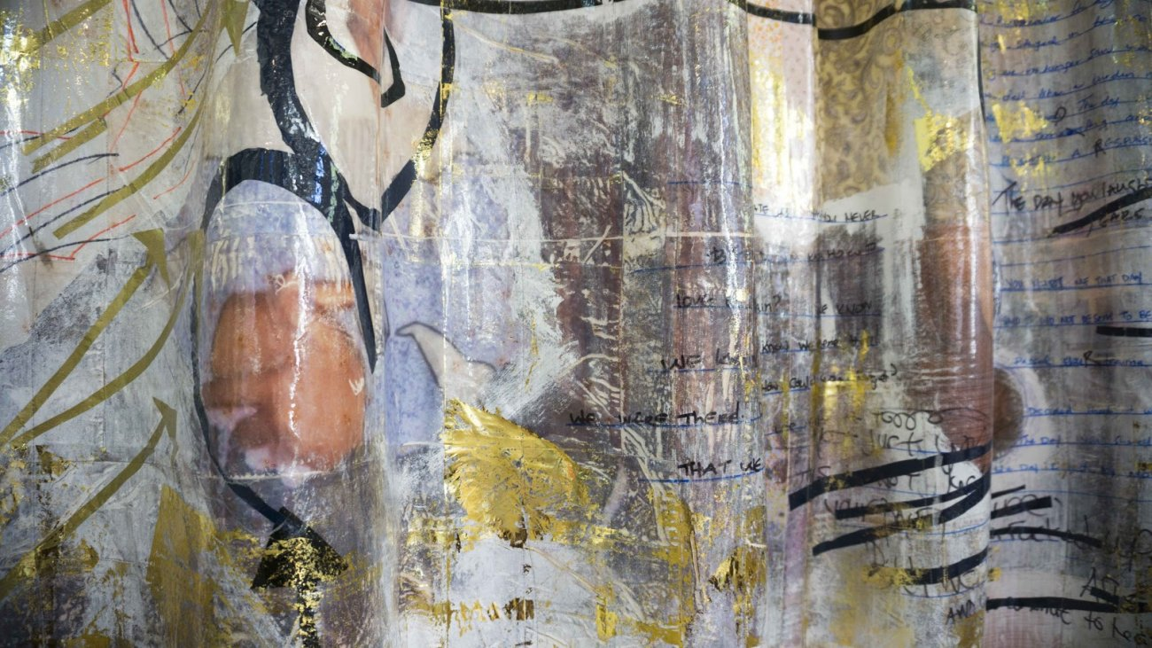 "Photograph of Stephanie Woods piece ""What Glitters Ain't Always Gold"", depicting mixed media including paint and text on a plastic material"