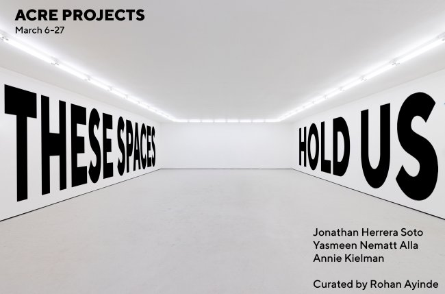 "Promotional image for exhibition depicting a white walled space with ""THESE SPACES HOLD US"" on the walls."